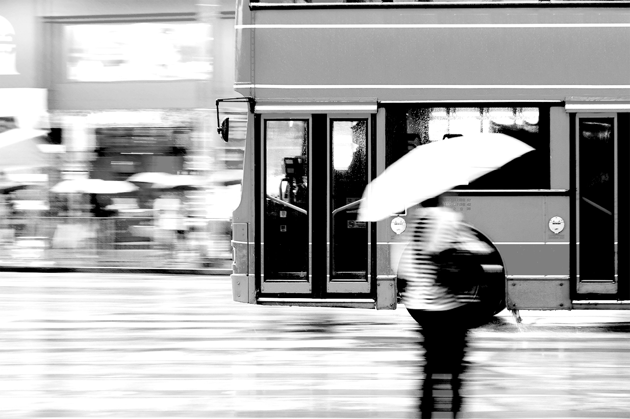 Bus driving by - black and white
